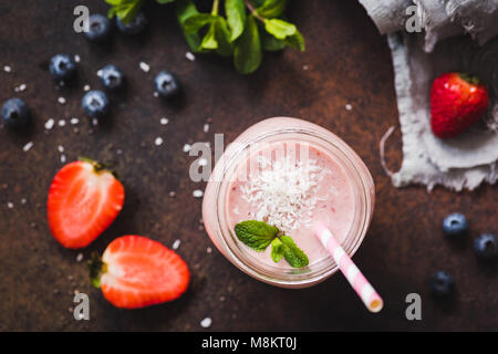 Strawberry coconut smoothie in jar with pink drinking straw, top view, selective focus. Healthy lifestyle, detox, - Stock Photo