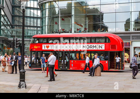 Man Sitting on a concrete bollard on Victoria Street , London ,as a no 11 Bus drives by with an Advertisement For - Stock Photo