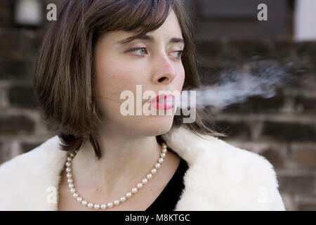 A well dressed woman wearing red lipstick and a pearl necklace, exhaling cigarette smoke. - Stock Photo