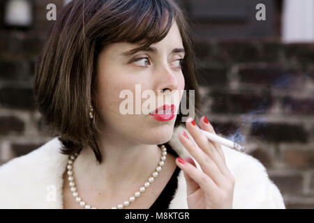 A well dressed woman wearing red lipstick and a pearl necklace, smoking a cigarette. - Stock Photo