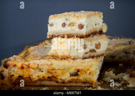 closeup two pieces of handmade  cheesecake with raisins stands on whole pie served on wooden tablet against gray - Stock Photo