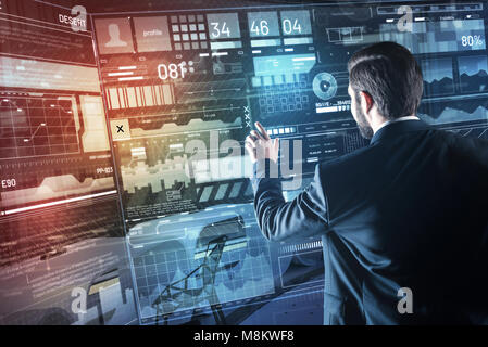Careful programmer looking at the screen while working with personal profiles - Stock Photo