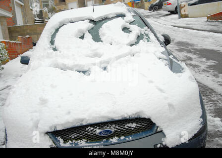 Portland, Dorset. 18th March 2018 - A cartoon face on a snow-covered car in Fortuneswell, Isle of Portland, Dorset - Stock Photo