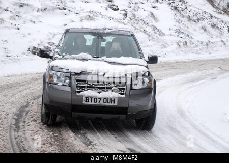 Cheddar Gorge, UK. 18th March 2018 - Land Rover Freelander 2 driving up Cheddar Gorge with snow Credit: Timothy - Stock Photo