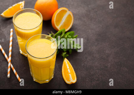Two glasses of freshly squeezed orange juice and mint on a dark brown background. Top view with copy space - Stock Photo