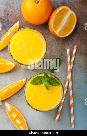 Two glasses with freshly squeezed orange juice and mint on an old rusty blue background. Top view - Stock Photo