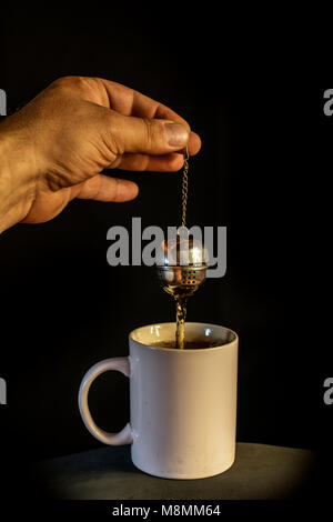 man's hand preparing tea in a bowl with infuser, on background - Stock Photo