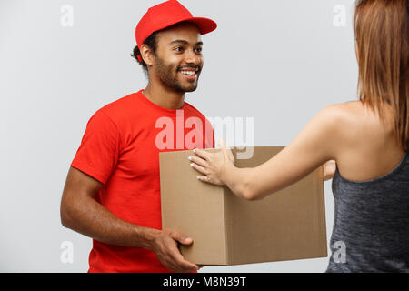 Delivery Concept - Handsome African American delivery man giving  package to homeowner. Isolated on Grey studio - Stock Photo