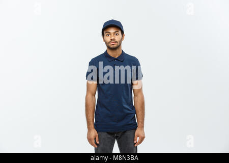 Delivery Concept - Handsome African American delivery man. Isolated on Grey studio Background. Copy Space. - Stock Photo