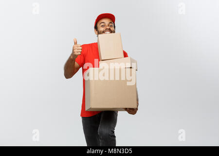 Delivery Concept - Portrait of Happy African American delivery man holding box packages and showing thumps up. Isolated - Stock Photo