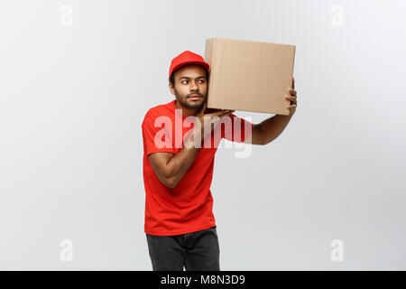 Delivery Concept - Portrait of Curious African American delivery man listen inside a box package. Isolated on Grey - Stock Photo