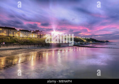 Sunburst over Cromer town - As dusk appears, the soft lights of streets and buildings come on. Cromer has one of - Stock Photo