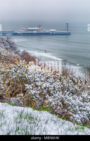 View over Bournemouth beach and Bournemouth pier covered in snow, Bournemouth, Dorset, England UK in March - Stock Photo