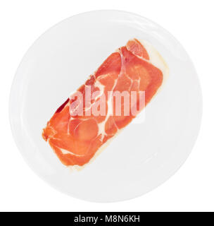 Single slice of raw italian prosciutto crudo, jamon on white plate isolated on white background. - Stock Photo