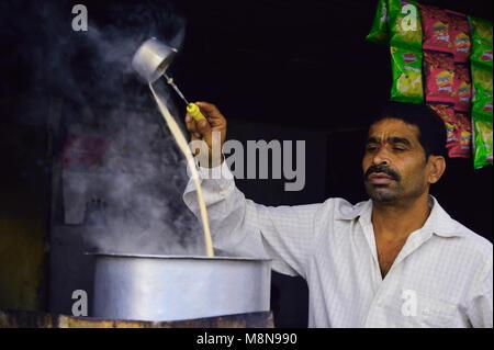 PUNE, MAHARASHTRA, INDIA 13 JAN 2018 . A local chai or tea maker pouring hot tea at a tea stall in Pune - Stock Photo