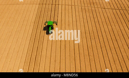 Farm hands work the aerators on a smooth well cultivated field