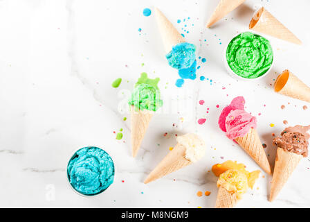 Different homemade melting ice cream in bowls and waffle ice cream cones, white vanilla, orange, pink berry, green, - Stock Photo