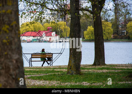 Lonely woman sitting alone on a bench in a pack near the lake - Stock Photo