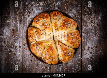 Bread buns with various seeds on vintage wooden table - Stock Photo