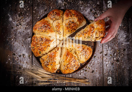 Fresh breakfast triangle buns with seeds on wooden background - Stock Photo