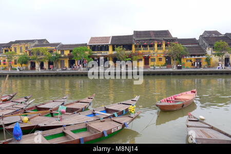 Hoi An, Vietnam - MARCH 17, 2018: Boats by the river in ancient town Hoi An with view of typical yellow houses - Stock Photo