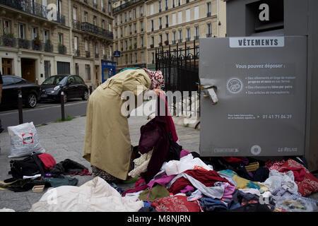 Woman Looking Through Charity Clothing Bin, Rue Saint-luc, La Goutte d'Or, 75018, Paris, France - Stock Photo