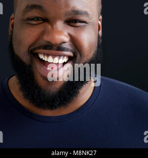 Close up of man laughing and smiling towards camera. - Stock Photo