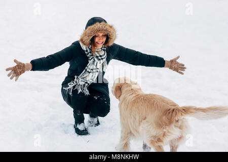 Image of girl hugging labrador in winter park for walk - Stock Photo