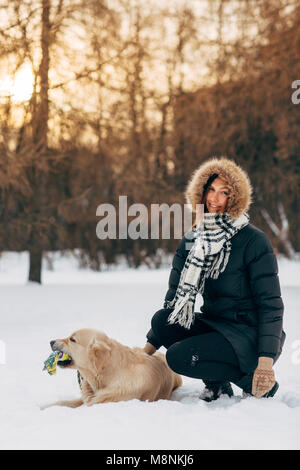 Photo of smiling girl with labrador on background of trees in winter park - Stock Photo