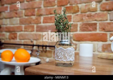 Rosemary branches in vase in kitchen - Stock Photo