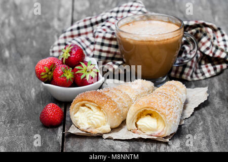 Puff  pastry horns with cup of cappuccino and strawberry on wooden table - Stock Photo
