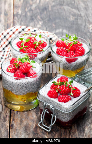 Chia  seed puddings with orange marmalade and raspberries on wooden table - Stock Photo