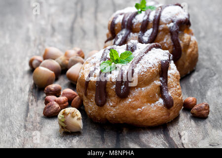 Belgian  chocolate choux buns stuffed with hazelnut cream on wooden table - Stock Photo