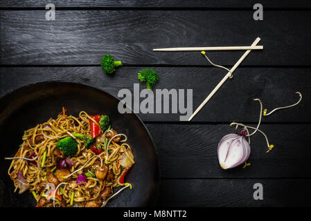 Udon stir fry noodles with meat or chicken. Served with chopsticks. Top view. - Stock Photo