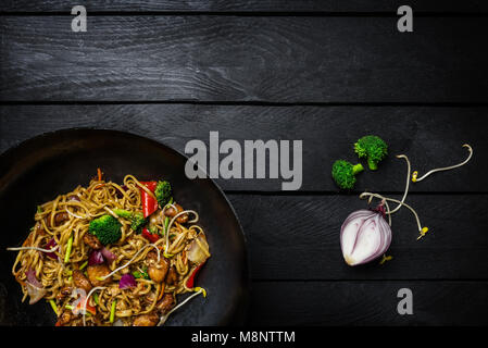 Stir fry noodles in traditional Chinese wok with ingredients. Space for text. - Stock Photo
