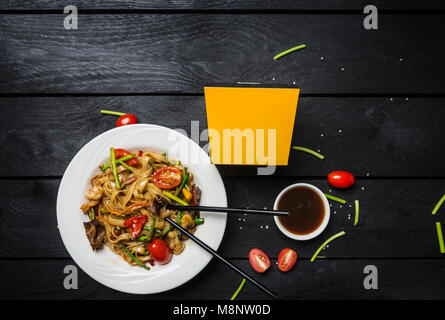 Udon stir fry noodles with seafood and mushrooms in a white plate on black background. With chopsticks and box for - Stock Photo