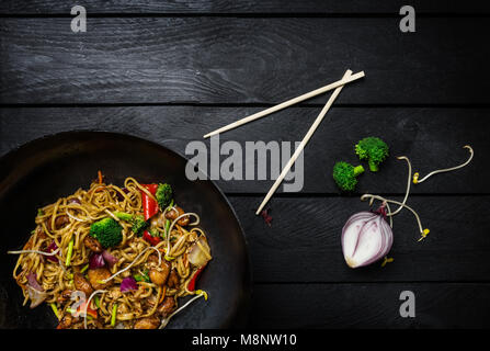Stir fry noodles in traditional Chinese wok, chopsticks and ingredients. Space for text. - Stock Photo