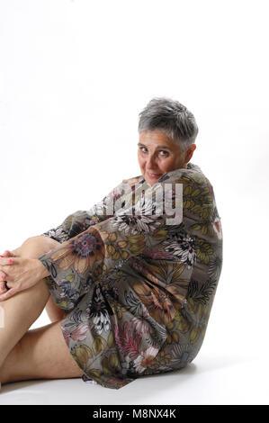 portrait of an elderly woman sitting on the floor - Stock Photo