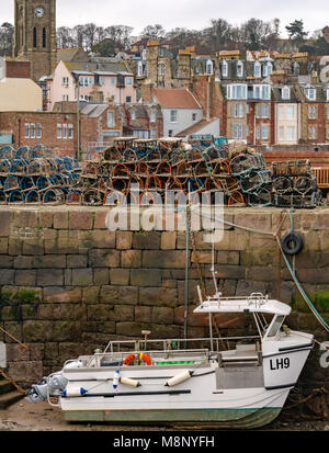 North Berwick, East Lothian, Scotland, United Kingdom,  Boat stranded in harbour at low tide with lobster creels - Stock Photo