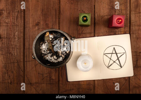 An overhead photo of a witch's cauldron, an open grimoire with a hand drawn pentacle, and candles. Wiccan ritual - Stock Photo