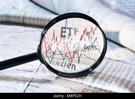 Magnifying glass shows the courses of ETF, funds and shares | usage worldwide - Stock Photo