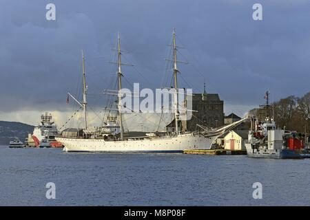 The training sailing ship Statsraad Lehmkuhl at the pier in Bergen's big harbour bay Vågen in front of a dark cloudy - Stock Photo