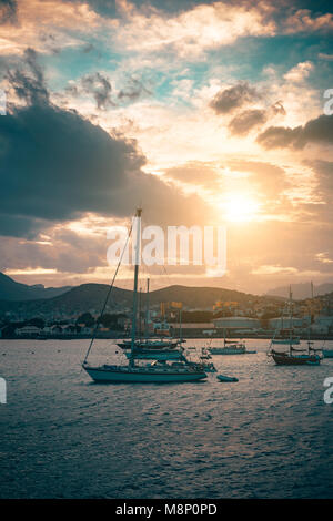 Sail Yacht on anchor in Mindelo Harbor on sunset. Golden flares light the cloudy sky. Sao Vicente Island, Cape Verde - Stock Photo