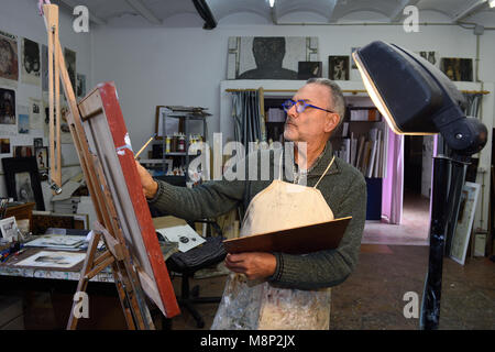Painter artist painting a picture in the studio - Stock Photo