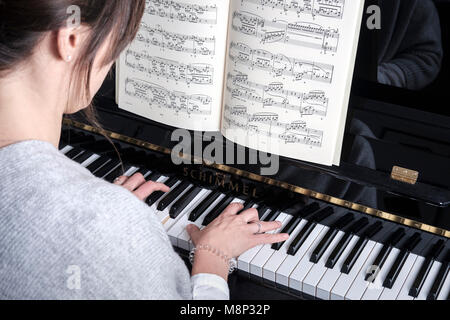 Woman plays  piano - selective focus,side view - Stock Photo