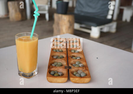 Ouril board game and Papaya Juice, beach bar in Tarrafal, Santiago Island, Cape Verde - Stock Photo