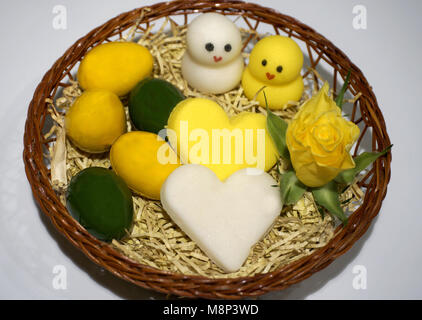 Easter decoration, chicken, hearts and eggs made from marzipan in the basket - Stock Photo
