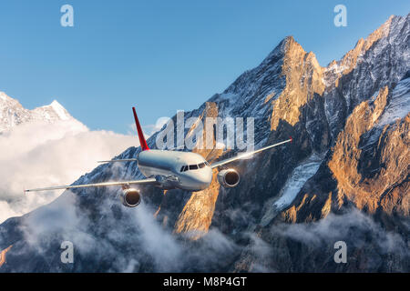 Airplane is flying over low clouds against mountains with snowy peaks in bright day. Landscape. Passenger airplane, - Stock Photo