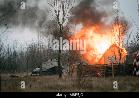 Red Army armored car passes near the burning building. Reconstruction of the liberation of the city of Gomel, Belarus - Stock Photo