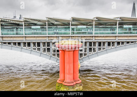 One of the tripled, red coloured pillars from the original Blackfriars railway bridge in front of the current railway - Stock Photo